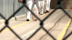 Prison Inmates Walking Fence - stock footage