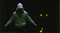 Athlete with a hooded top skips intensely at night Stock Footage