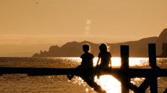 Two Children Sitting On Bridge At Sunset - stock footage