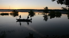 Silhouette of fishermen fishing off a small boat during sunrise Stock Footage