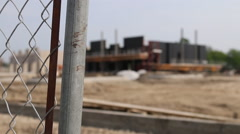 Rack focus from a fence to a building at a commercial construction site Stock Footage