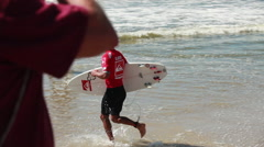 Kelly Slater runs into the ocean, Quiksilver Pro New York Surf Competition Stock Footage