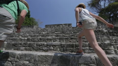Couple climbs the Xunantunich temple in Belize Stock Footage