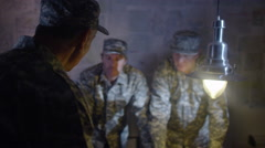 4K Military officers in army bunker, looking at map & discussing battle strategy Stock Footage