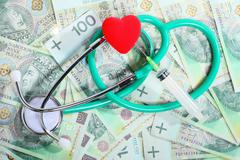 cost of health care: stethoscope red heart polish money - stock photo