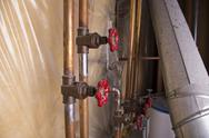 Stock Photo of Home plumbing pipes and wiring.