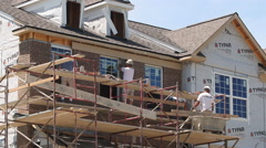Bricklayers build up a wall on a new townhome under construction Stock Footage