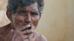Ndian man smokes a cigar and looks into the camera, 1080p HD Stock Footage