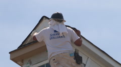 A painter paints the roof peak on a new townhome under construction Stock Footage