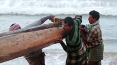 Indian fishermen push a traditional wooden fishing boat out of the water Stock Footage