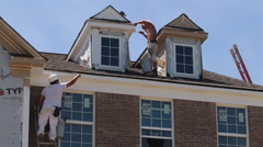 Painters paint a new home under construction Stock Footage