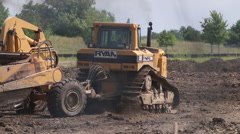 Caterpillar construction vehicles excavate a building site - stock footage