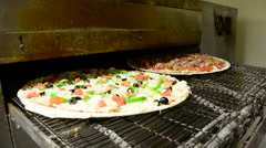 A veggie and meat lovers pizza go into a restaurant oven Stock Footage