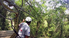 Young woman rides zip-line Stock Footage