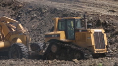 Caterpillar construction vehicles excavate a building site Stock Footage