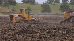 Caterpillar bulldozers and soil compactors excavate soil at a building site - stock footage