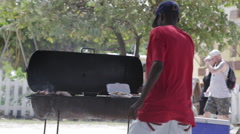 An unidentified man barbeques' on the beach at Terry's Grill Stock Footage