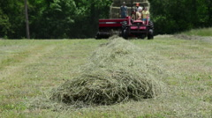 Farmers on a red tractor bail hay on a farm, generic HD farming - stock footage