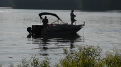 Silhouette of two men fishing from a small boat, 1080p HD fishing Stock Footage