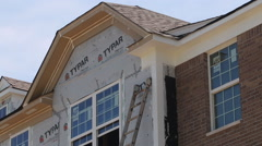A painter climbs a ladder to paint a window of a new townhome Stock Footage