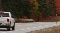 Tilt up from pickup truck driving on a New England road to trees in the fall 4K - stock footage