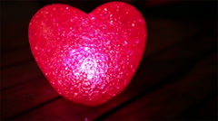 Glowing Neon Heart on dining table at night Stock Footage