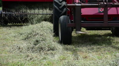 A red tractor bails hay on a farm, generic HD farming Stock Footage