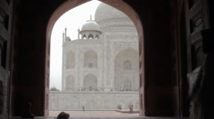 Indian men walk through a mosque doorway with the Taj Mahal in the background Stock Footage