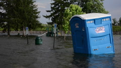 A Porta Kleen porta potty floats in a parking lot after flood Stock Footage