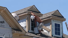 A painter paints the peak of a roof on a new townhome Stock Footage