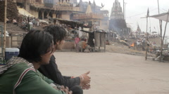Indian men chat outside a burning ghat near the Ganges river Stock Footage