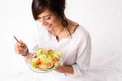 Healthy Eating Woman Enjoys Raw Food Fresh Green Salad - stock photo