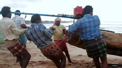 Indian fishermen pull a traditional wooden fishing boat out of the water Stock Footage