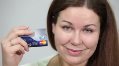 Smiling happy woman showing MasterCard credit card in hands and looking at cam Stock Footage