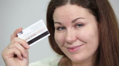 Smiling happy woman showing credit card in hands and looking at camera Stock Footage