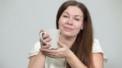 Young adult woman holding tea mug in hands, looking at camera, grey background Stock Footage