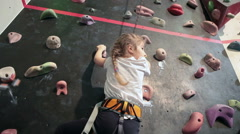 Little girl with assistance rope falling down from climbing wall, bouldering - stock footage