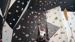 The rock-climbing train with child on the wall and mother assistance, gym Stock Footage