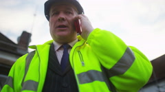 4K Mature male engineer or architect makes a phone call at construction site Stock Footage