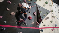 Young girl conquer the wall in gym with climbing equipment - stock footage