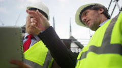 4K Mature engineers or architects checking on progress at construction site - stock footage