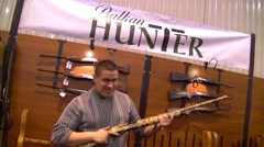 Stock Video Footage of Man holding gun on  fishing and hunting  fair