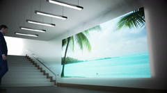 Businessman looking at screen showing beach paradise Stock Footage