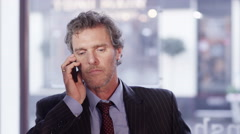 4K Angry businessman has a heated conversation with someone on the phone Stock Footage