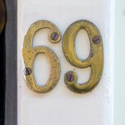 Gold colored house number sixty nine - 69 Stock Photos