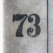 Black house number seventy three, painted on stone -  73 Stock Photos
