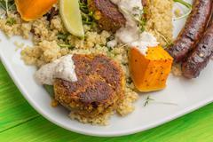 Quinoa with roasted pumpkin, falafel and sausages Stock Photos