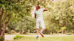In slow motion cool young break dancer doing back flip in the park Stock Footage