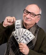Lucky elderly man holding dollar bills Stock Photos