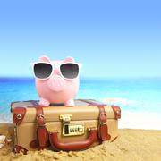 Suitcase with piggy bank in sunglasses on tropical beach Stock Photos